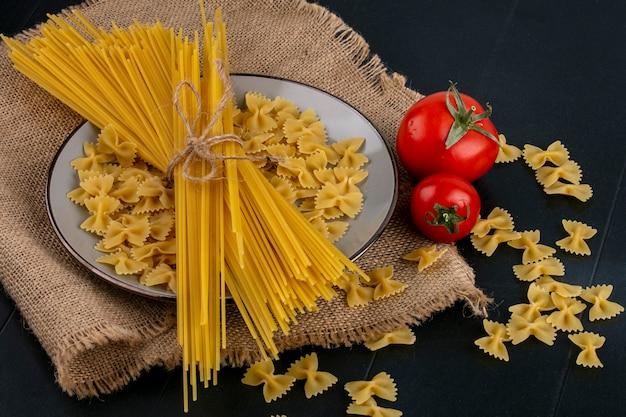 Вид сбоку сырой пасты с сырыми спагетти и помидорами на бежевой салфетке на черной поверхности