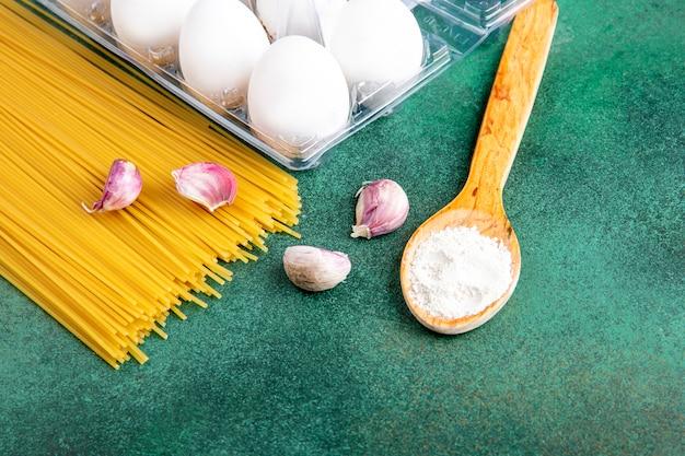 Вид сбоку сырых спагетти с чесноком и яйцами деревянной ложкой с мукой на зеленой поверхности
