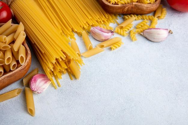 Вид сбоку сырых спагетти с сырой пастой в мисках с чесноком на серой поверхности