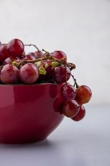 Вид сбоку красного винограда в миске на клетчатой ткани на сером фоне