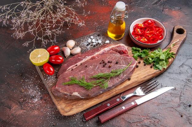 木製のまな板に赤身の肉と暗い背景にニンニクグリーンレモンみじん切りピーマントマトオイルボトルの側面図