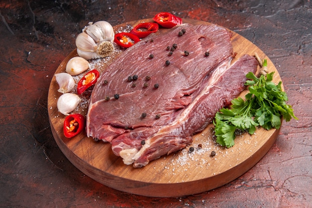 Вид сбоку красного мяса на деревянном подносе и чеснока, зеленого лимона, лука на темном фоне