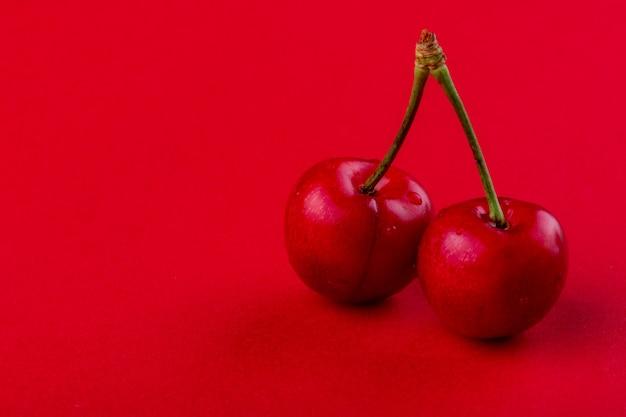Вид сбоку красной спелой вишни с каплями воды, изолированных на красном с копией пространства