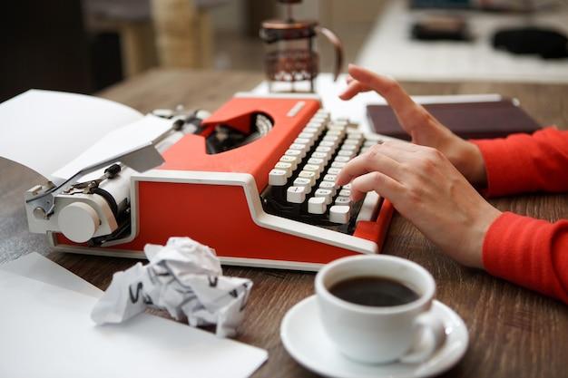 Вид сбоку красной пишущей машинки, чашка кофе, мятой бумаги