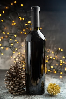お祝いのための赤ワインボトルと暗い背景の上の2つの針葉樹の円錐形の側面図