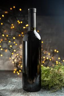 暗い背景でお祝いのための赤ワインボトルの側面図