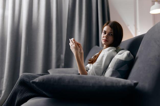Вид сбоку рыжеволосой женщины с телефоном, сидящей на диване