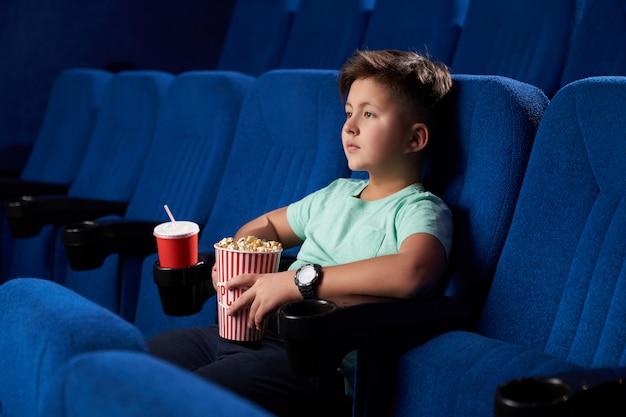 Вид сбоку расслабленной мужской подростков едят нездоровую пищу в кино