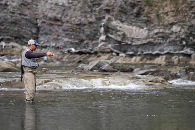 Вид сбоку расслабленного человека в водонепроницаемой одежде, неподвижно стоящего в реке во время рыбалки. горная природа. понятие об активном образе жизни.