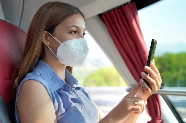 スマートフォンアプリを使用してkn95ffp2フェイスマスクでリラックスした女性の側面図。携帯電話でテキストメッセージを移動する保護マスク付きのバスの乗客。公共交通機関で安全に旅行してください。