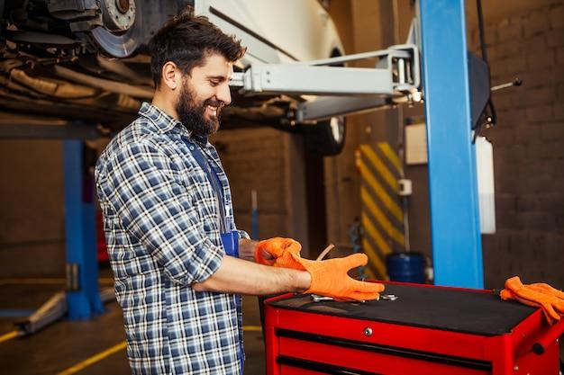ガソリンスタンドで車で作業するために手袋を着用している修理工の男性の側面図
