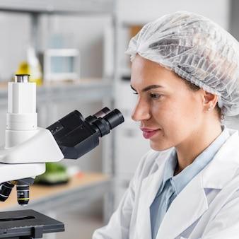 Вид сбоку исследователя в лаборатории биотехнологии с микроскопом