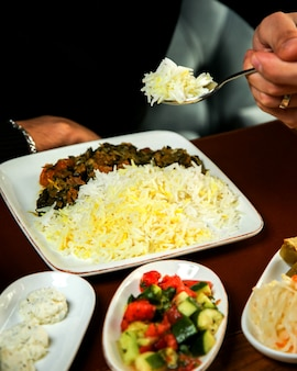 나무 테이블에 조림 고기와 허브와 쌀의 측면보기
