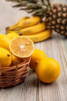 白い壁の上の灰色の木製のテーブルに分離されたレモンバナナとパイナップルとバケツの上の豊富なビタミンレモンの側面図