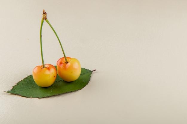Вид сбоку спелой желтой вишни с зеленым листом на белом с копией пространства