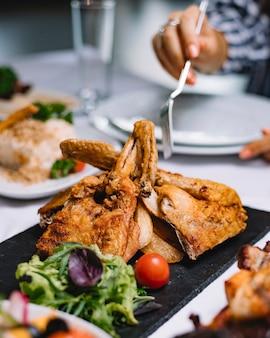 Вид сбоку жареной курицы с травами и помидорами черри на черной доске