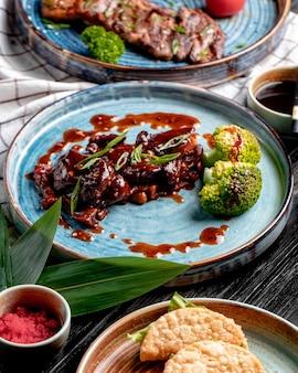 Вид сбоку жареной курицы с кисло-сладким соусом и брокколи на тарелке на клетчатой скатерти