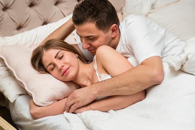 ベッドに抱かれたロマンチックなカップルの側面図