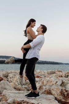 Романтическая пара, держащая друг друга на берегу океана, вид сбоку