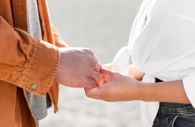屋外で手をつないでロマンチックなカップルの側面図