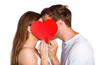 Side view of romantic couple holding heart