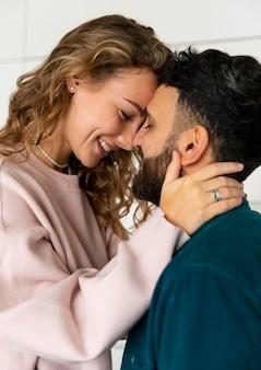 家でキスするロマンチックなカップルの側面図