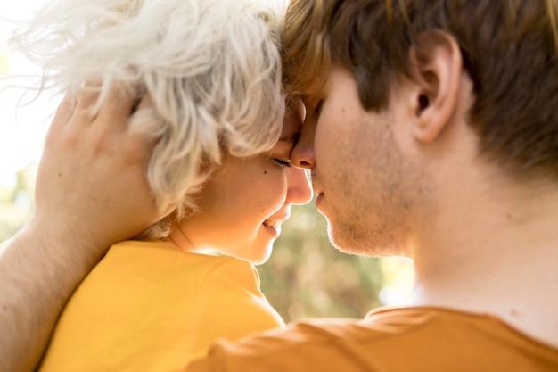 屋外の公園でロマンチックなカップルの側面図