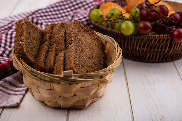 Вид сбоку ломтиков ржаного хлеба в корзине на клетчатой ткани с корзиной виноградных нектакотов на деревянном фоне