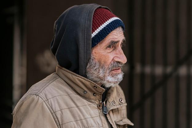悲しいひげを生やしたホームレスの男性の側面図