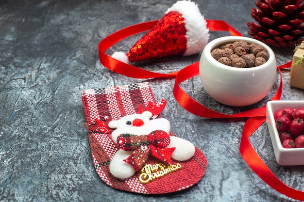 暗い表面にサンタクロースの帽子とコーネルチョコレート新年の靴下赤い針葉樹の円錐形の贈り物の側面図