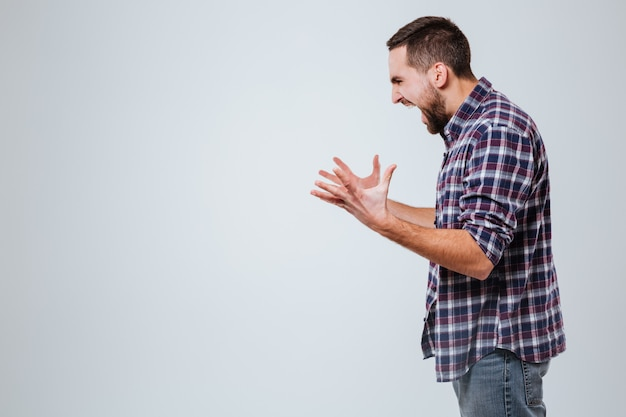 Вид сбоку кричащий бородатый мужчина в рубашке