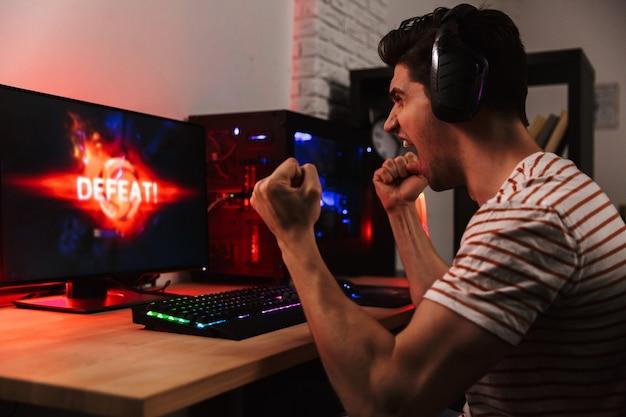Вид сбоку на кричащего недовольного геймера, играющего в видеоигры