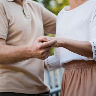 Вид сбоку пожилой пары, взявшись за руки на открытом воздухе