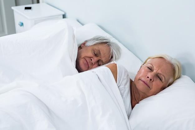 ベッドで寝ている年配のカップルの側面図