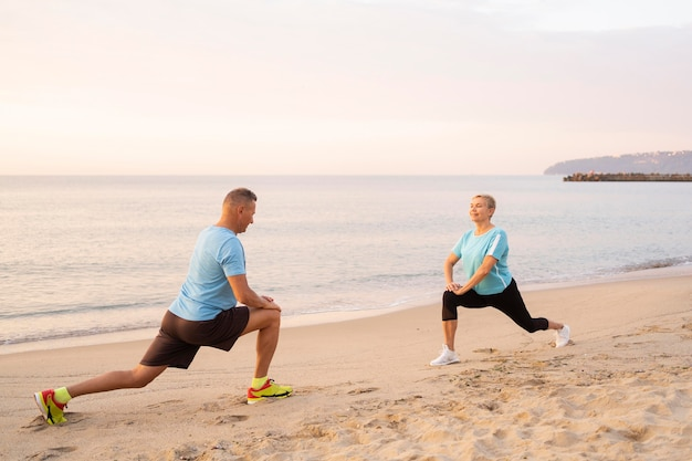 一緒にビーチでストレッチシニアカップルの側面図