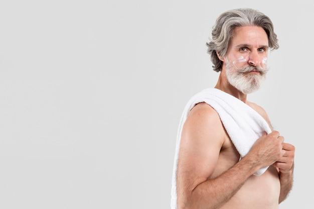 タオルでシャワー後の年配の男性の側面図