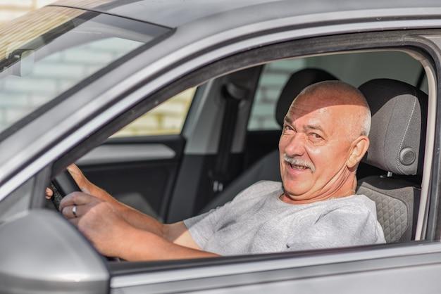 Вид сбоку старшего мужчины за рулем автомобиля