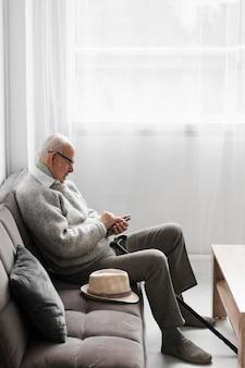 Вид сбоку пожилого человека в доме престарелых с помощью смартфона