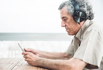 Side view of senior man looking at mobile phone listening music on headphone
