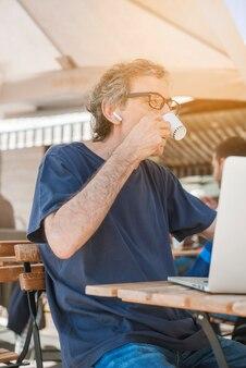 屋外のカフェでノートパソコンを飲む高齢者の側面図