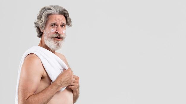 シャワーと保湿剤の後のタオルで年配の男性人の側面図