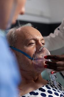 병원 집중 치료에서 호흡 튜브에 의해 도움이되는 노인 환자 호흡의 측면보기. 아프리카 의사와 간호사가 노인 호흡 노래 얼굴 마스크를 돕는.