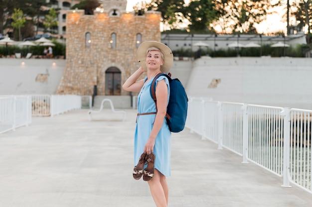 Взгляд со стороны старшей туристской женщины держа ботинки