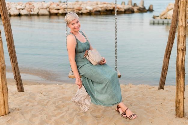 ビーチのブランコに乗るシニア観光客女性の側面図