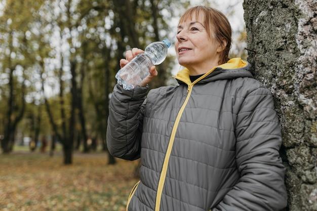 屋外で運動した後の水を飲む年配の女性の側面図