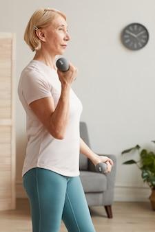自宅の部屋でダンベルで運動する年配の女性の側面図