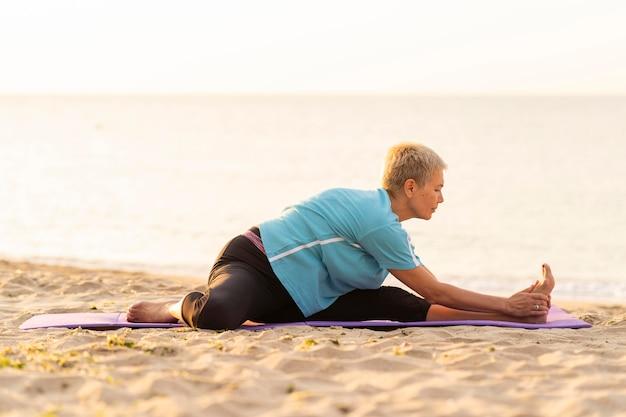 ビーチでストレッチ年配の女性の側面図