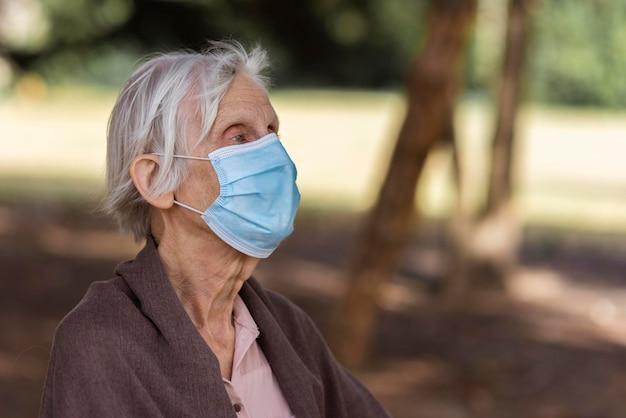 의료 마스크 야외 및 복사 공간 고위 여자의 측면보기