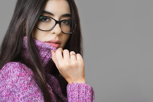 따뜻한 니트 스웨터와 회색 배경에 서있는 동안 카메라를보고 세련된 안경에 관능적 인 여성의 측면보기