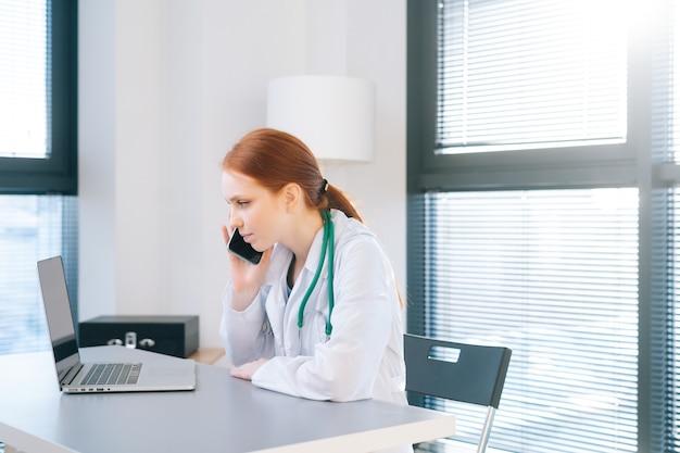 晴れた日の窓の背景にある医療クリニックの机に座ってラップトップで入力し、携帯電話で話している白衣を着た深刻な忙しい女性医師の側面図。